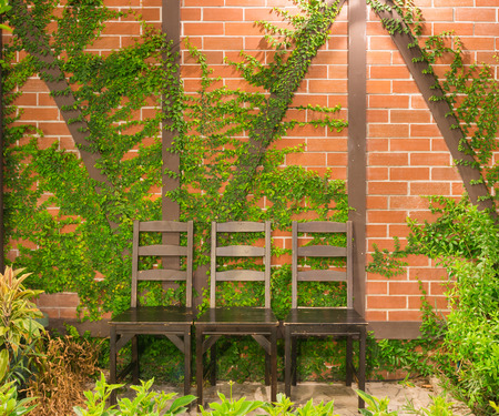 close up three wood desk chair on red bric wall background in garden photo