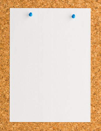close up Blank white paper note sheet with blue push pin on cork board background for write memo photo