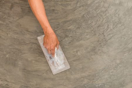 Close up of hand using steel trowel to finish wet concrete floor of polished concrete surface