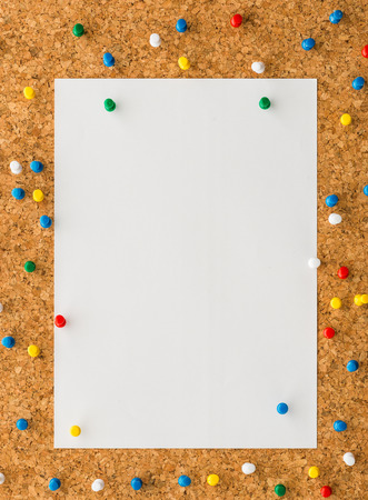 cork sheet: close up Blank white paper note sheet with multicolored push pin on cork board background for write memo