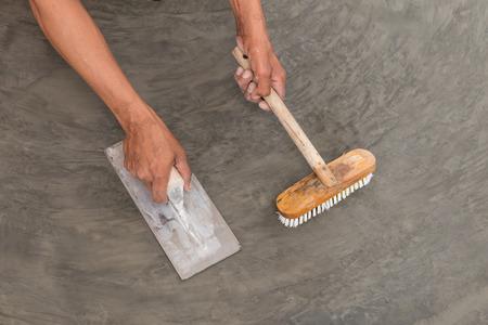 concrete: Primer plano de la mano con llana de acero para terminar de piso de concreto mojado de la superficie de hormigón pulido