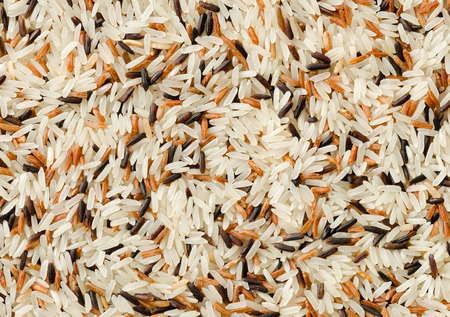 Food background with three mixed of Thai rice varieties : brown rice, mixed wild rice, white (jasmine) rice. species Oryza sativa. Stockfoto