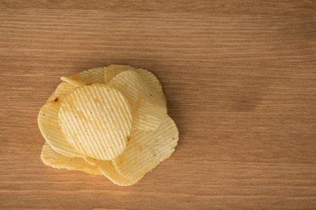 serrate: crispy potato chips on the wood table background