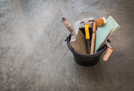 materiales de construccion: de cerca herramientas de construcción para trabajo concreto en cubo de plástico negro en el fondo de la superficie de hormigón pulido Foto de archivo