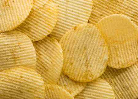 and fat: crispy potato chips on the wood table background