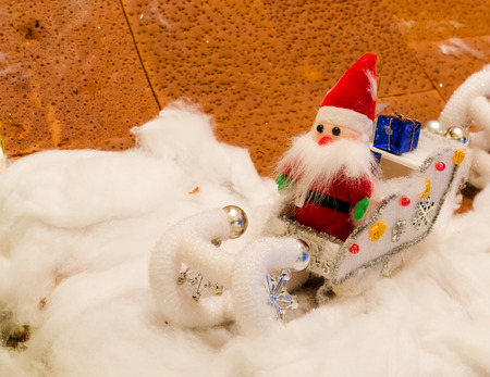 santaclaus: doll of Santa Claus sitting on car  in snow