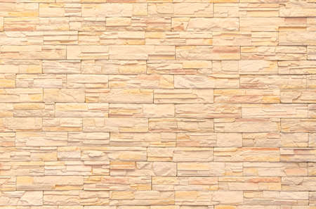 background and texture of yellow decorative  stone wall surface. modern style design decorative uneven cracked stone texture wall surface with cement. Banque d'images