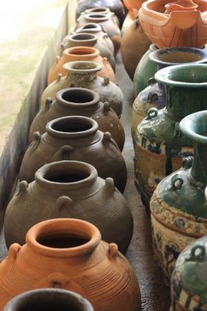 Lots of old clay black pots on floor photo