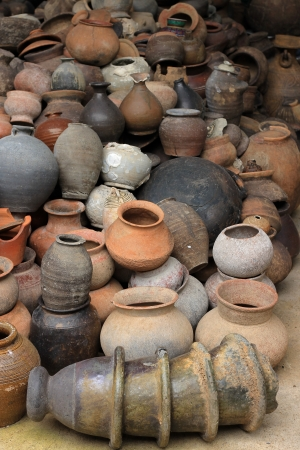 Lots of old clay black pots on floor photo