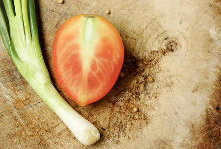 Tomato and spring onion wood background
