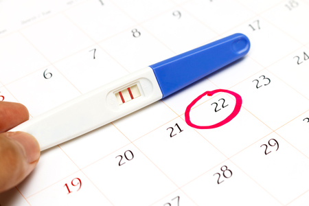 assign: Pregnancy test with positive result lying on calendar Stock Photo