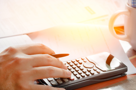 savings, finances, economy and home concept - close up of man with calculator counting making notes at home, soft focus.