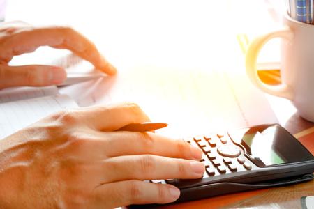 Ahorro, las finanzas, la economía y el hogar concepto - cerca del hombre con el conteo calculadora que hace notas en el hogar, enfoque suave. Foto de archivo - 63090951