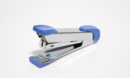 Old blue stapler on white, soft focus