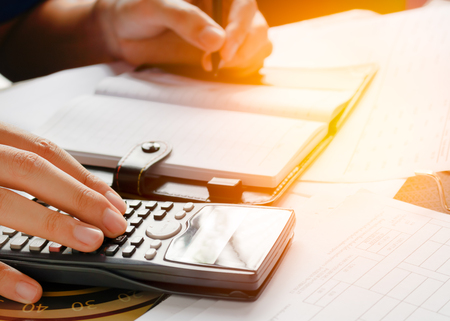 close up, business man or lawyer accountant working on accounts using a calculator and writing on documents, soft focus Standard-Bild