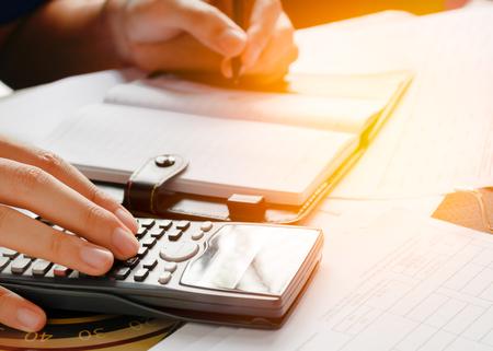 de cerca, el hombre de negocios o un contador abogado que trabaja en las cuentas con una calculadora y escritura en los documentos, enfoque suave