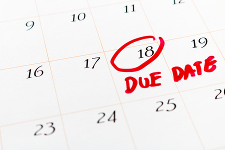 The big Due Date day, the 18th, Red circled mark on a white calendar, as a reminder of the date your project must be completed and submitted or the date you expect to deliver your baby, soft focus.