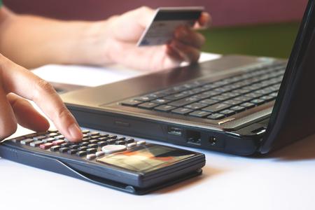 besparingen, financiën, economie en kantoorconcept, berekenen hoeveel kosten of uitgaven hebben met creditcards. Weinig licht, kan worden gebruikt voor e-commerce, laptop, business, technologie en internet concept, soft focus. Stockfoto