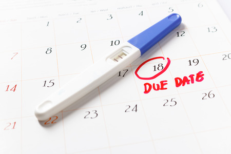 Pregnancy test with positive result lying on calendar; Due Date day; the 18th; Red circled on a white calendar; soft focus. Stock Photo