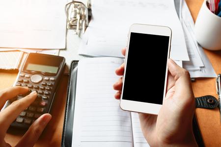 Close up de empresario utilizando teléfono móvil con sceen en blanco para la búsqueda de datos y calculadora contando haciendo notas y en la oficina o el hogar.