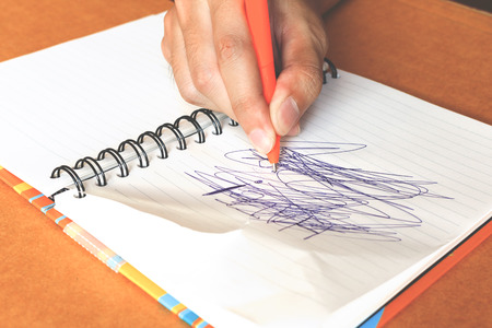 labyrinthine: female hands with pen writing labyrinthine on notebook