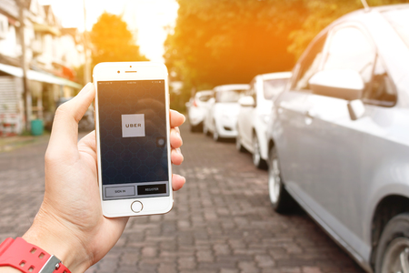 CHIANG MAI,THAILAND - SEP 02,2016 : A woman hand holding Uber application startup page on the Apple iPhone 6 display in female hand. Blurred street view with car,Uber is smartphone app-based transportation network.