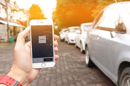 CHIANG MAI, Tailandia - SEP 02,2016: Una mano de la mujer la celebración de Uber página de inicio de la aplicación en la pantalla de Apple iPhone 6 en la mano femenina. Vista de calle borrosa con el coche, Uber es la red de transporte basada en app smartphone. Editorial