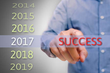 bussinessman: bussinessman hand pointing success text for 2017. targets concept