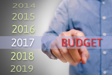 bussinessman: bussinessman hand pointing budget text for 2017. targets concept