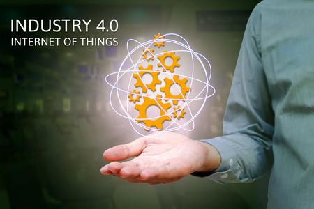 業界 4.0、男こと概念の産業インターネットは、歯車のアイコンと工場背景を持つネットワークを示しています。