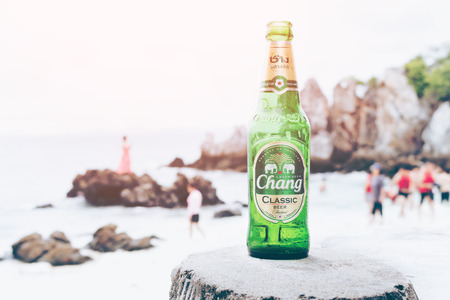KHAI NAI ISLAND,THAILAND-OCTOBER 8, 2016: The New Chang Beer Bottle on wood chair on the beach, Thai people like to drink, Thailands largest and one of Southeast Asias largest beverage companies