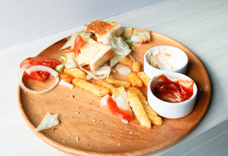 wasted: Junk food is wasted or spoiled food and other refuse, in wood dish from a kitchen. Stock Photo