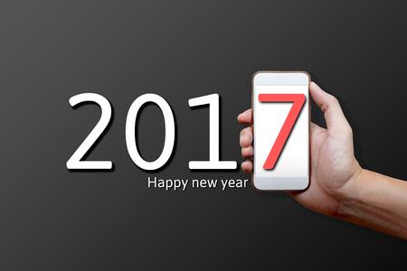 2017 Concepto de Feliz Año Nuevo, Parte del cuerpo, Mano sosteniendo el teléfono móvil y el número siete en la pantalla.