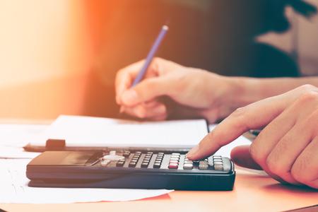 Ciérrese encima de mujer joven con la cuenta de la calculadora que hace notas en casa, la mano se escribe en un cuaderno. Ahorro, finanzas, concepto.