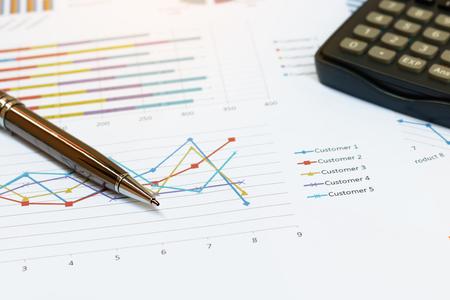 cuadro sinoptico: Cierre de concepto de negocio, la pluma es el informe de síntesis y la calculadora en la oficina de mesa. Foto de archivo