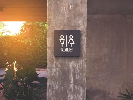 unisex: Unisex restroom or toilet label on concrete post.