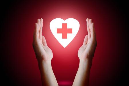 donacion de organos: el concepto de salud, la mujer mano que sostiene y protege el corazón con el símbolo médico en el interior sobre fondo rojo.