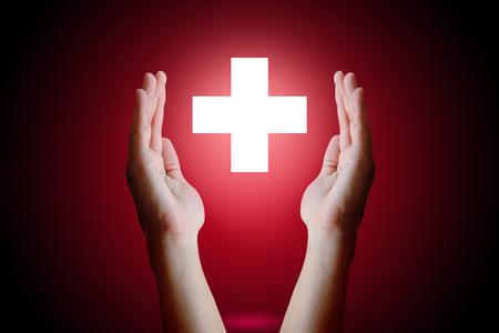 Concepto de salud, mano de mujer sosteniendo y proteger símbolo médico sobre fondo rojo. Foto de archivo - 69678002