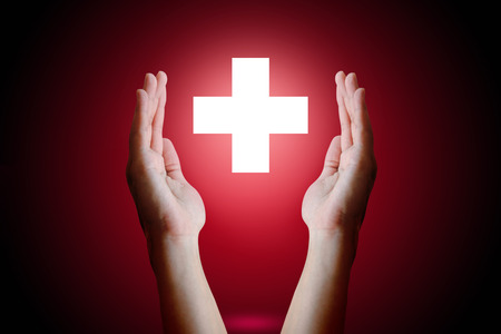 Healthcare concept, Woman hand holding and protect medical symbol on red background. Imagens