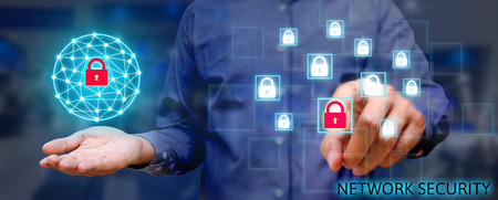 Concepto de red de seguridad cibernética, Joven hombre asiático sosteniendo la seguridad de red global y presionando icono de bloqueo con pantalla virtual. Foto de archivo