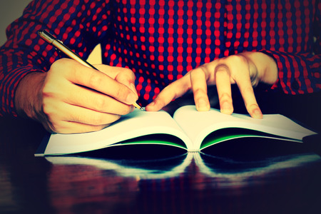 organise: Man hand writing on notebook on desk in home. Stock Photo