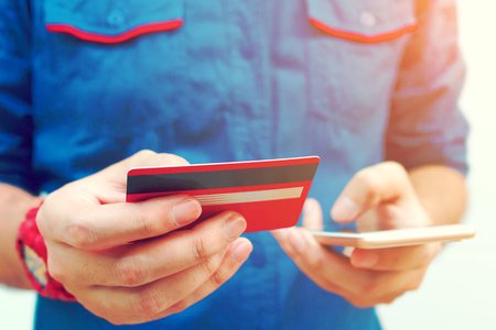 hands free phone: Young man use smartphone and holding credit card with shopping online. Stock Photo