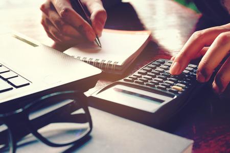 Ciérrese encima de la mano de la mujer usando la calculadora y escribiendo anote con calcular sobre costo en la oficina en casa.