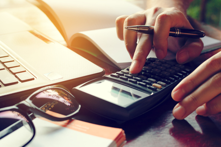 Close up man calculate cost on desk at home. Banque d'images