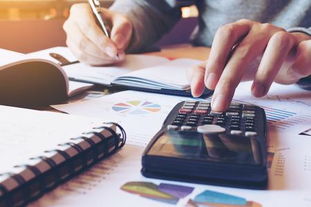 Chiuda sull'uomo della mano che fa la finanza e calcoli sullo scrittorio circa l'ufficio di costo a casa. Archivio Fotografico - 73102687