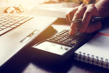 La calculadora con el hombre de la mano calcula finanzas en la oficina del escritorio en el país. Foto de archivo - 72813438