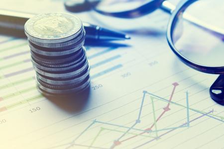 Informe resumido y concepto de análisis financiero, pluma y cuaderno con moneda de Tailandia y anteojos en el informe de papel. Foto de archivo - 74624313