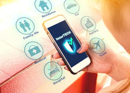 Insurance technology (Insurtech) concept, woman looking data information on smartphone. Standard-Bild