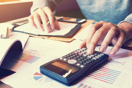 ploblem: Asian woman pressing calculator and thinking about ploblem cost for company. Stock Photo