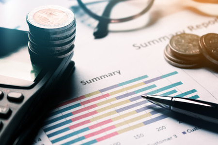Summary report and business equipment managing financial on desk with finance savings concept.